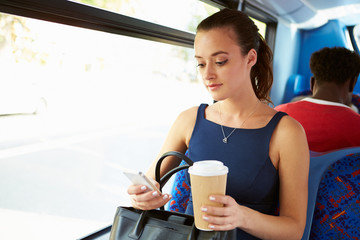 Businesswoman Sending Text Message On Bus