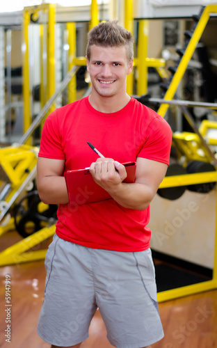 Young male personal trainer writing on clipboard smiling