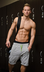 Shirtless muscular young male athlete in gym dressing room