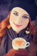 Redhead girl with red coffee cup.