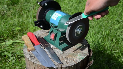 hand turns electric sharpener outside sharpen the blade