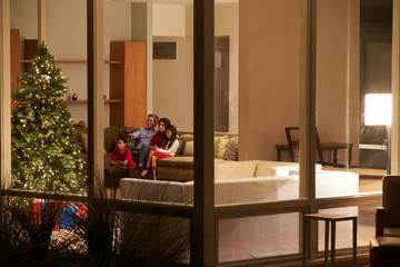 Family Watching Christmas TV At Home Viewed From Outside