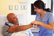 Nurse Putting Wristband On Senior Male Patient In Hospital - 59150195