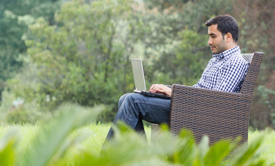 Profile of a young man with laptop, outdoor - outside