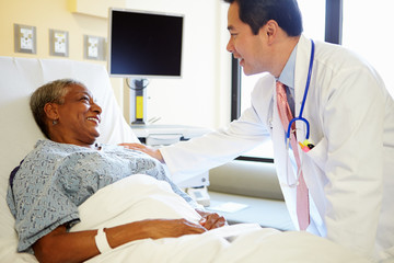 Doctor Talking To Senior Woman In Hospital Room