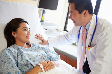 Doctor Talking To Female Patient On Ward