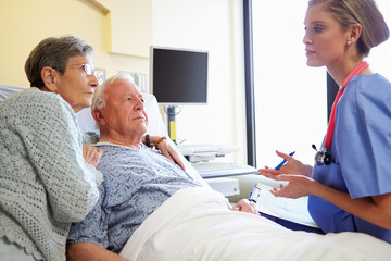 Nurse Talking To Senior Couple In Hospital Room