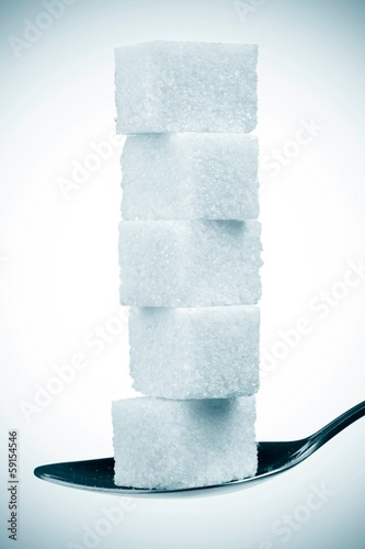 stack of sugar cubes in spoon. isolated on white