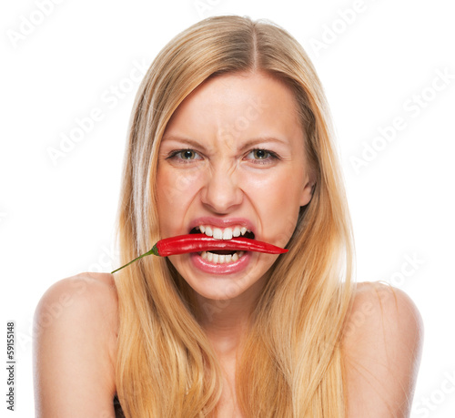 Teenage girl with red chili pepper in mouth