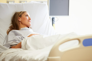 Female Patient Resting In Hospital Bed