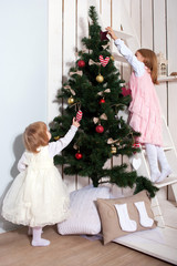 Two little girls decorating the Christmas tree.