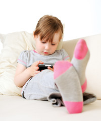 l Baby sitting on a couch at home playing and touching a mobile