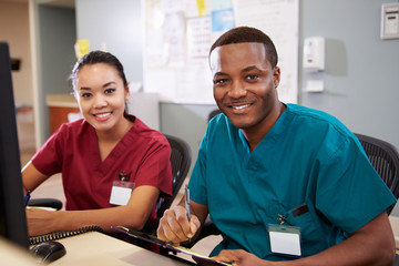 Male And Female Nurse Working At Nurses Station