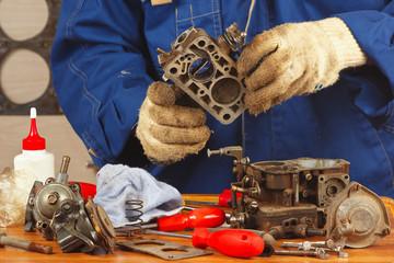 Mechanic repairing the old car engine carburetor