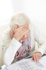 Unhappy senior woman looking at financial bill