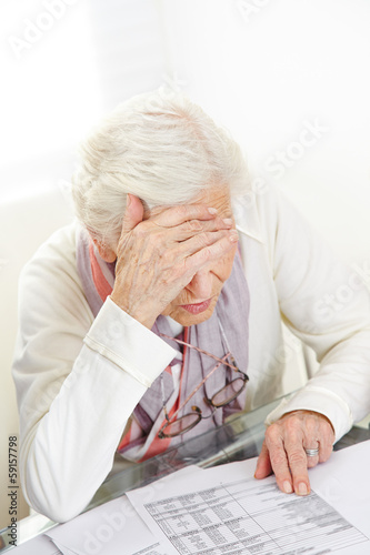 Unhappy senior woman looking at financial bill