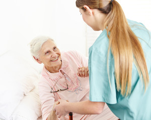 Nurse at extended home care helping senior