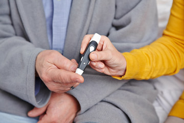 Senior man with diabetes getting blood glucose monitoring