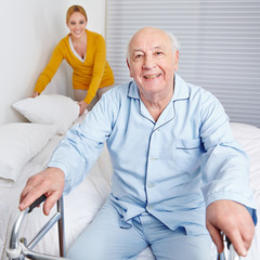 Woman fixing bed for senior man in family