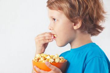 Cut child eating popcorn on a white background