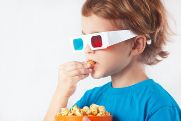 Young ironic boy in stereo glasses eating popcorn