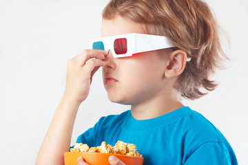 Little boy in stereo glasses with bowl of popcorn