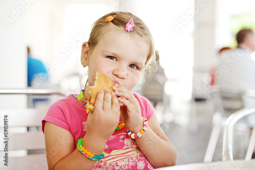 little girl with hamburger
