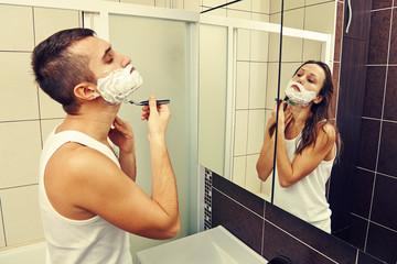 man shaving and looking at a woman