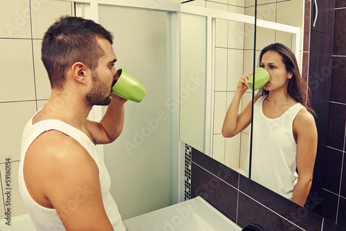man drinking tea and looking at a woman