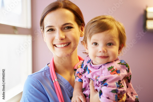 Young Girl Being Held By Female Pediatric Nurse