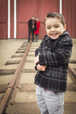 Mixed Race Boy at Train Depot with Parents Smiling Behind