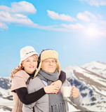 Mature smiling couple holding a cup and posing outside in snowy