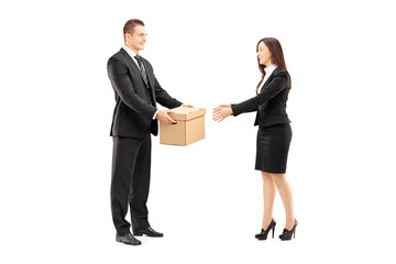 Young businessman giving a box to his female colleague