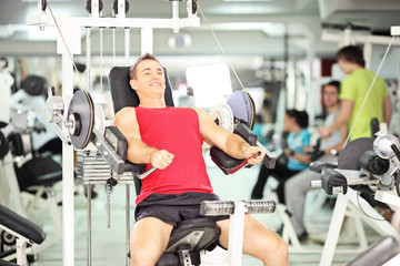 Smiling muscular young man exercising in a club