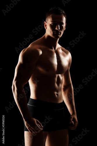 Shirtless muscular guy looking at camera