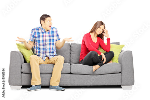 Young heterosexual couple sitting on a couch during an argument
