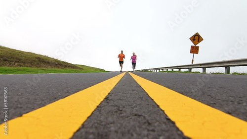 Young fit couple running down road over camera