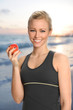 Young Woman Holding Apple on Beach