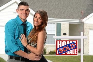 Happy Couple if Front of Newly Sold Home