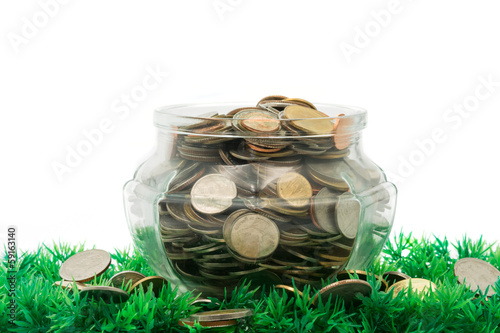glass jar full of bath coins on artificial grass