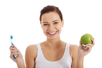 Beautiful woman with apple and toothbrush.