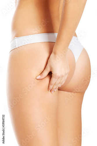 Young woman is touching her skin on buttock.