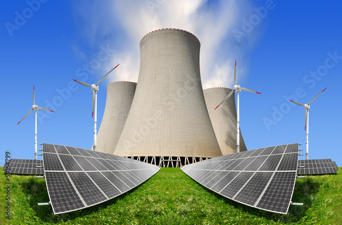 Solar panels before a nuclear power plant and wind turbines