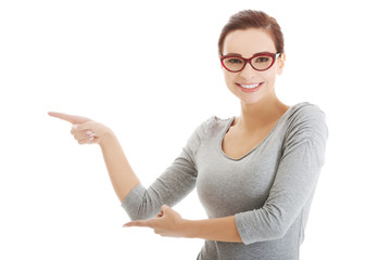 Beautiful casual woman in eyeglasses pointing aside.