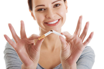 Young beautiful woman holding broken cigarette.