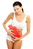 Beautiful slim woman holding hot water bottle.