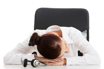 Young beautiful business woman on call center is sleeping on tab