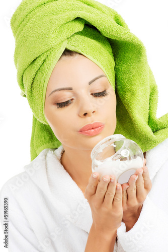 Beautiful woman in bathrobe, turban and holding face cream.