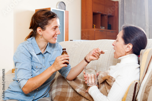 Adult daughter giving the liquid medicament to  mother