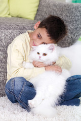 boy with a white Persian cat at home